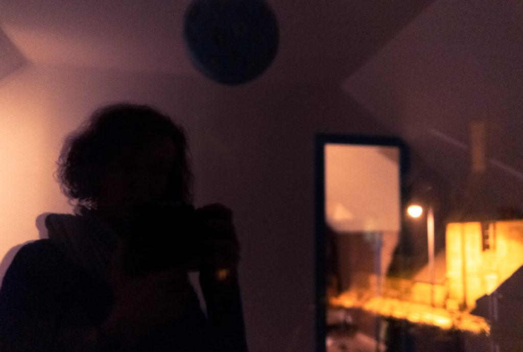 Mes autoportraits en 2019. Autoportrait la nuit, reflet dans une fenêtre mêlant à la fois la lumière froide de l'intérieur et la lumière chaude de l'extérieur. Photographe Pascaline Michon.