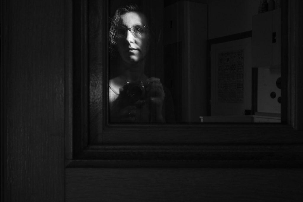 Mes autoportraits en 2019. Autoportrait de reflet dans une porte en noir et blanc. Photographe Pascaline Michon.