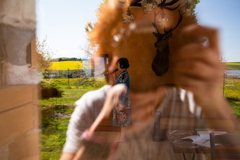 Mes autoportraits en 2019. Autoportrait dans le reflet d'une baie vitrée. Lecture multiple entre intérieur et extérieur. Photographe Pascaline Michon.