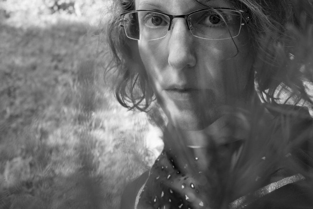 Mes autoportraits en 2019. Autoportrait dans le jardin à travers des feuillages. Noir et blanc. Photographe Pascaline Michon.