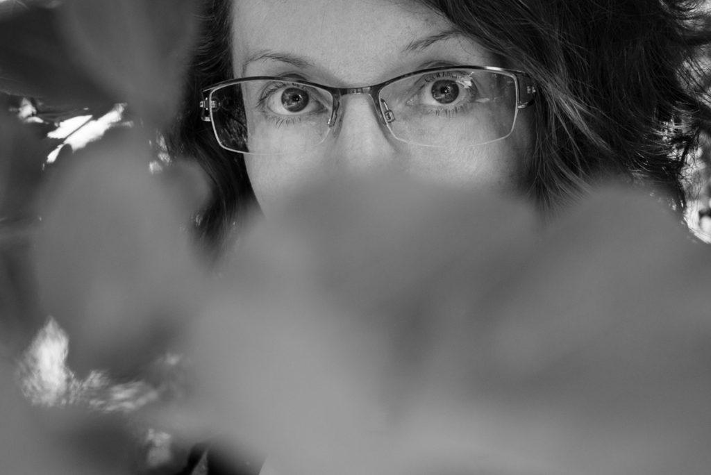 Mes autoportraits en 2019. Autoportrait dans le jardin, juste le regard le reste caché par des feuillages. Noir et blanc. Photographe Pascaline Michon.