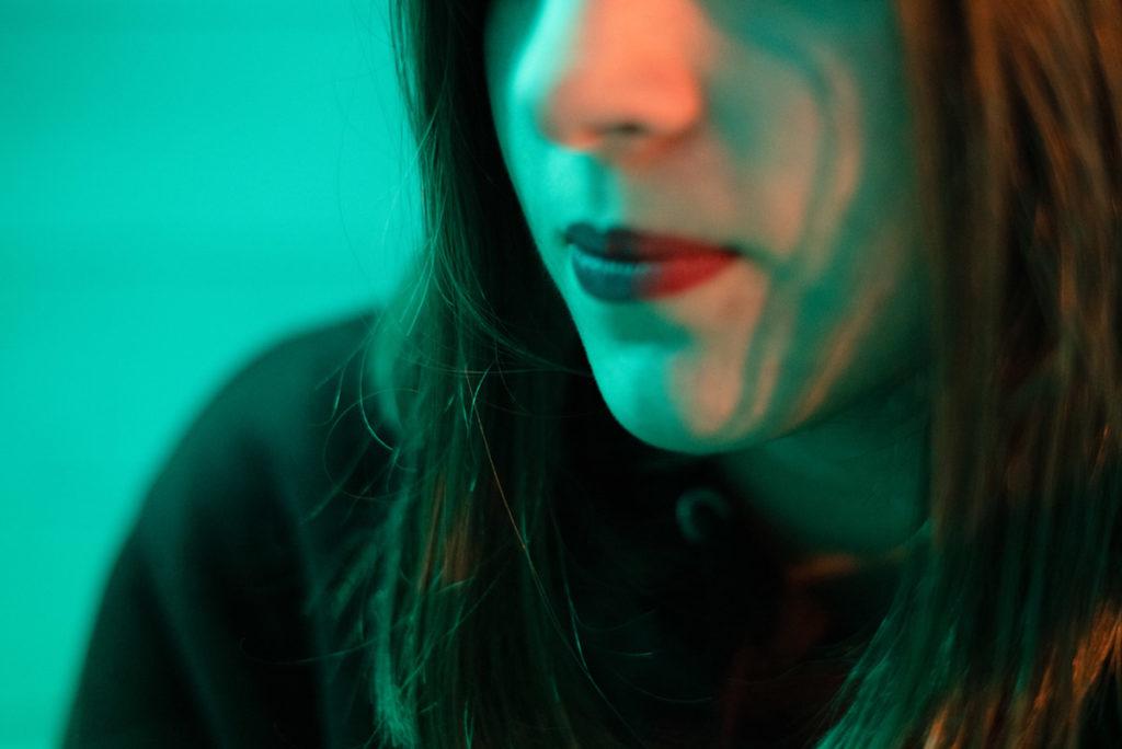 Portraits en lumière colorée. Portrait serré et cadré avec le bas du visage. Portrait réalisé avec une lumière colorée verte. Beaucoup de flou. Photographe Pascaline Michon.
