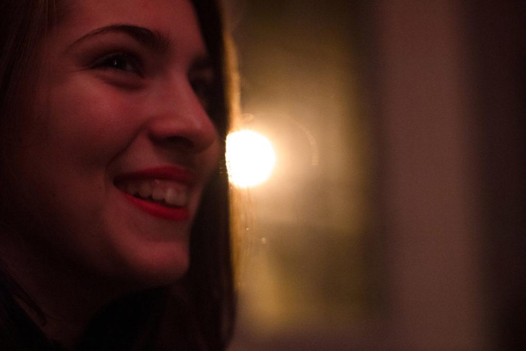 Portraits en lumière colorée. Portrait d'une ado en contre-jour. La lumière extérieure forme un halo à la fenêtre. Ambiance colorée jaune. Photographe Pascaline Michon.