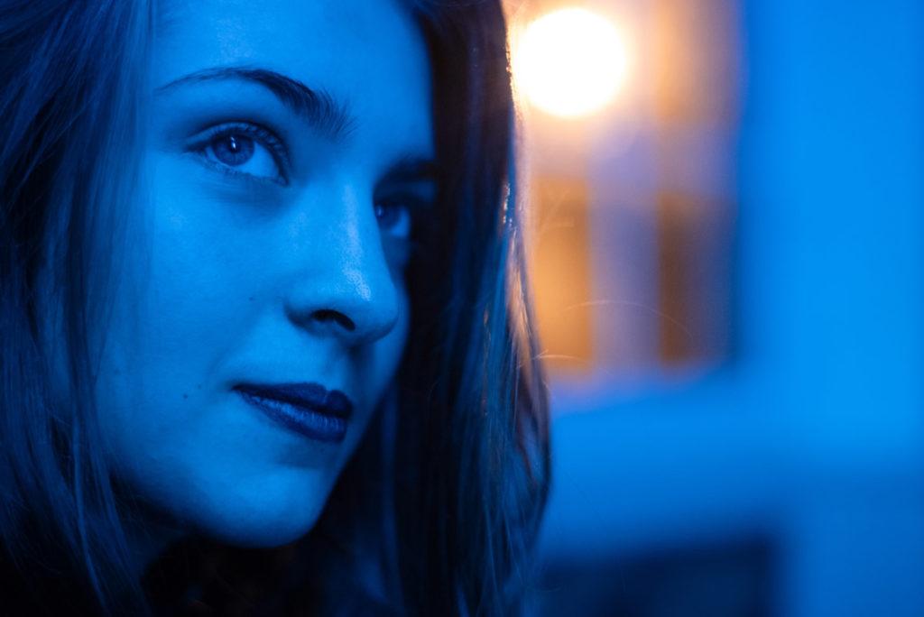 Portraits en lumière colorée. Portrait d'une ado dans une ambiance bleutée. Contraste avec la lumière orangée visible par la fenêtre. Photographe Pascaline Michon.