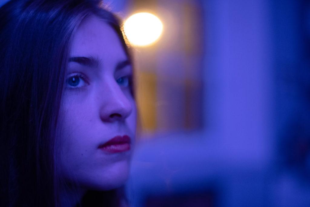 Portraits en lumière colorée. Portrait d'une ado dans une ambiance colorée entre bleu et violet. La faible profondeur de champ confère un caractère très doux au portrait. Photographe Pascaline Michon