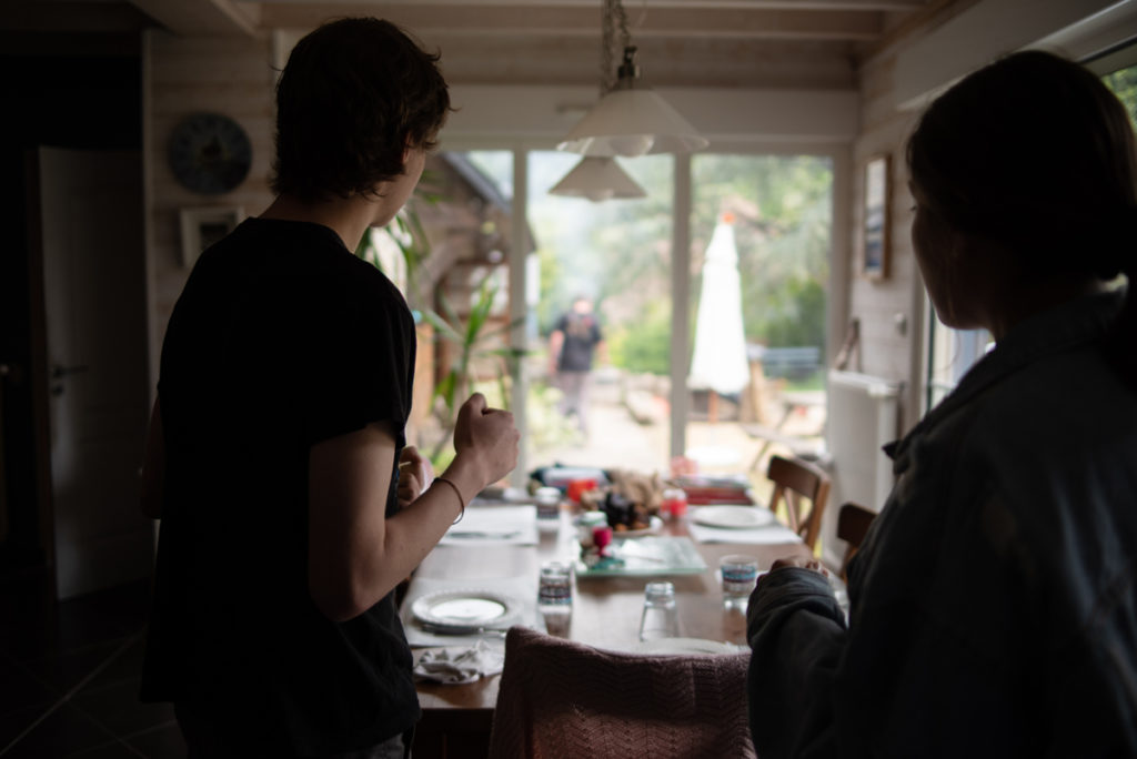 Défi photo le 24 du mois. Deux ados regardent leur père préparer un barbecue.