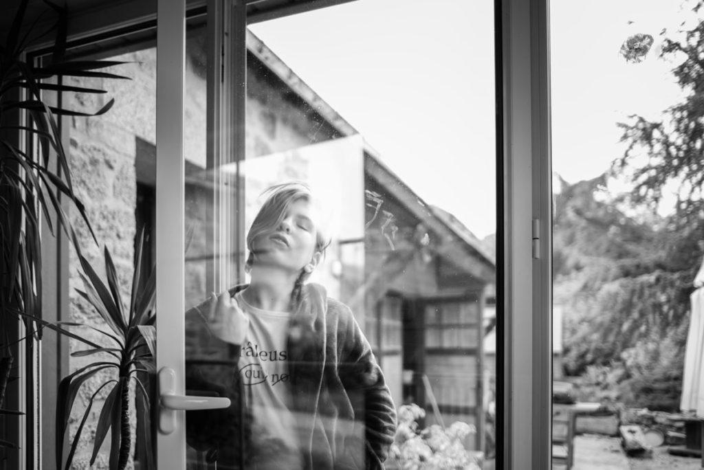 Photo d'une jeune fille rêveuse à travers la fenêtre. Noir et blanc. Documenter son quotidien heure par heure.