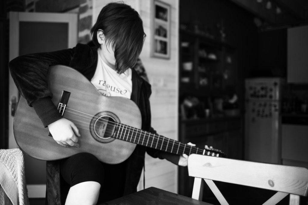 Défi photo le 24 du mois. Jeune fille jouant de la guitare.