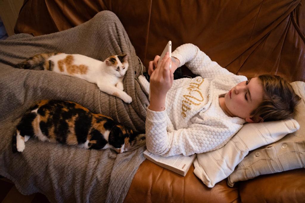 Réussir des portraits naturels de ses enfants. Moment câlin d'une jeune fille avec ses chats.