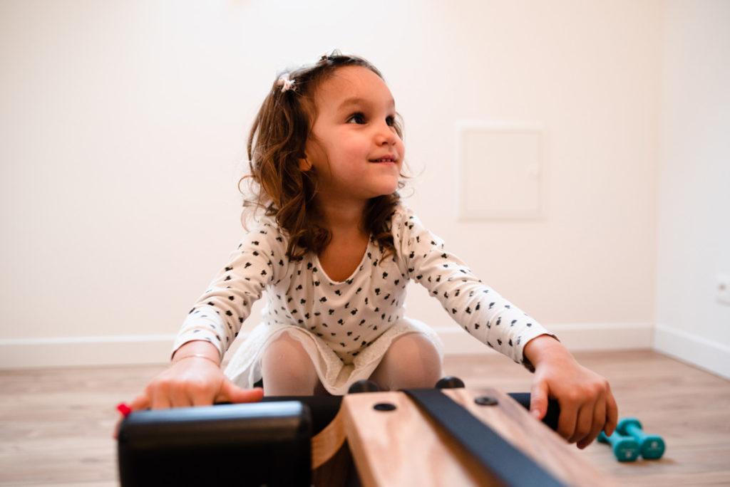 Réussir des portraits naturels de ses enfants. Une petite fille joue sur un rameur en bois avec résistance à eau.