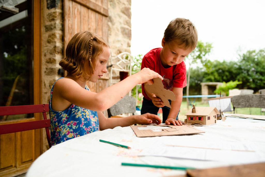 Réussir des portraits naturels de ses enfants. Portrait d'enfants qui construisent une petite maison en carton.