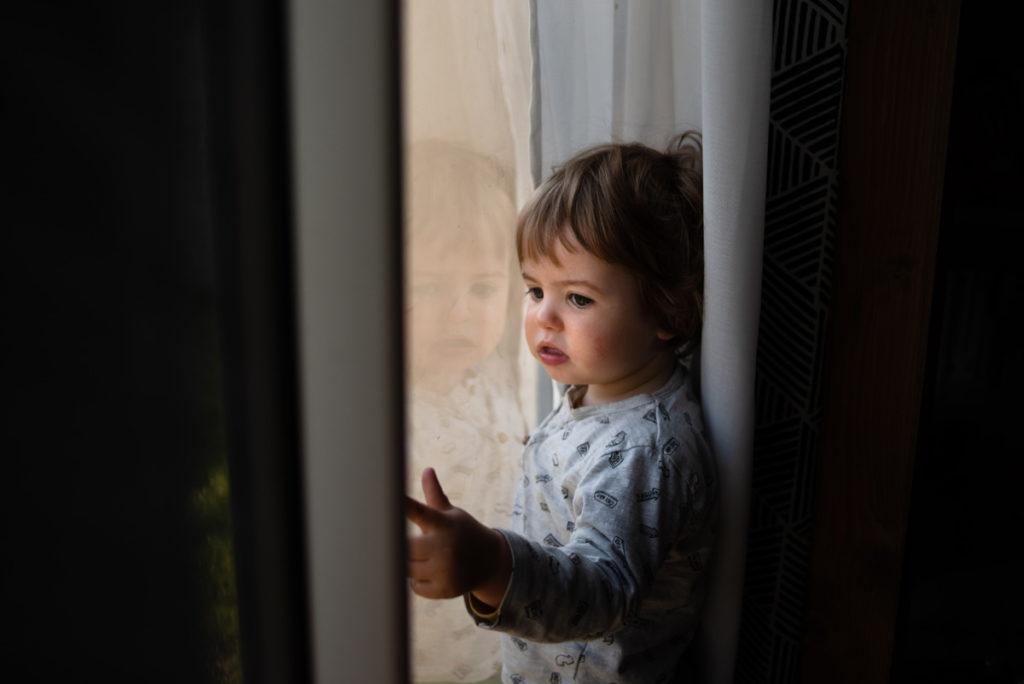 Portrait d'un jeune enfant à la fenêtre.