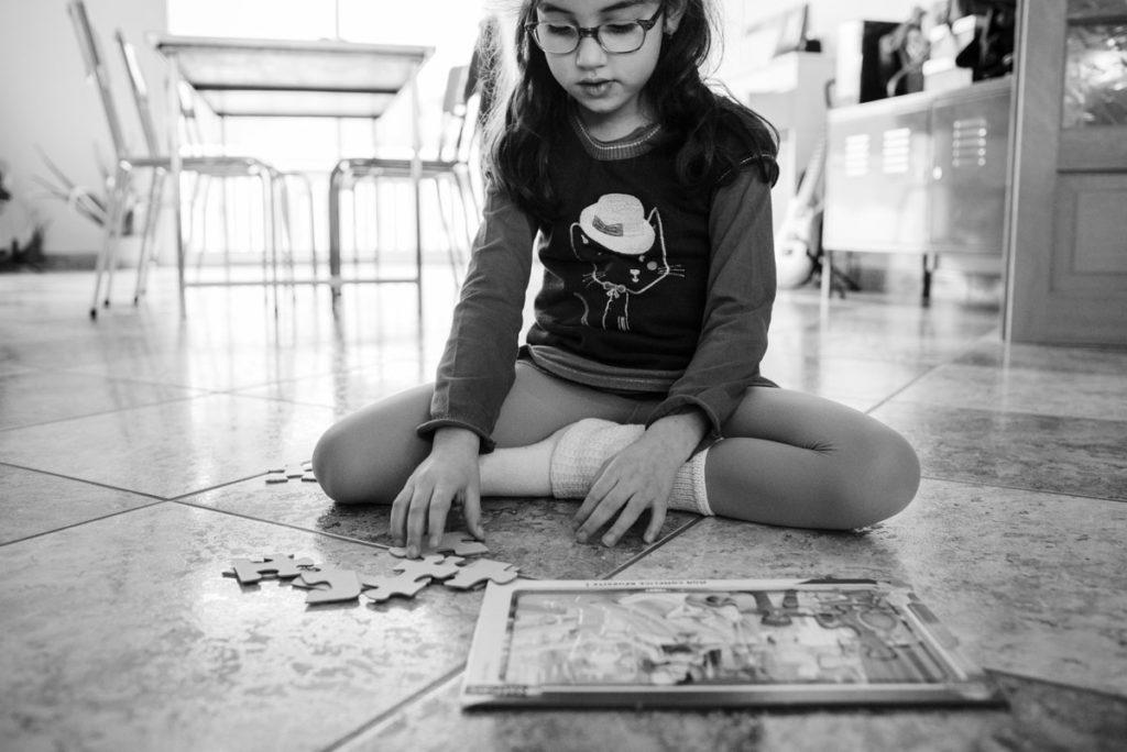 Portrait en noir et blanc. Enfant faisant un puzzle.