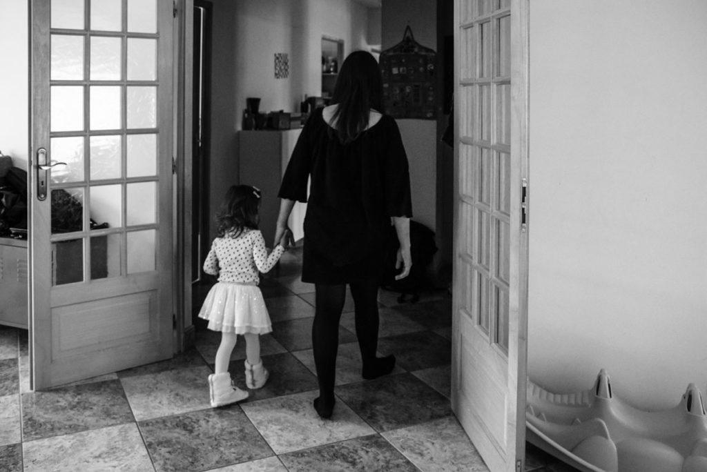 Portrait en noir et blanc d'une maman et sa fille se tenant par la main.